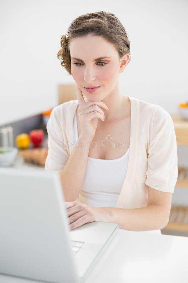 Seduta calma attraente della donna premurosa davanti al suo computer portatile fotografie stock