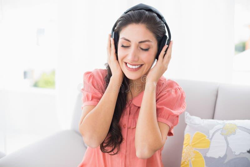 Seduta castana calma sul suo sofà che ascolta la musica immagine stock