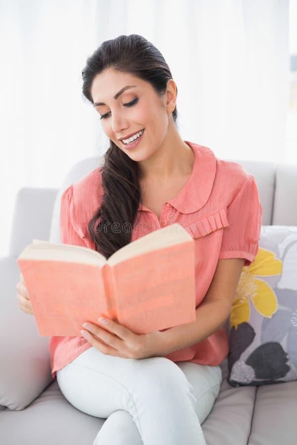 Seduta castana contenta sul suo sofà che legge un libro fotografia stock