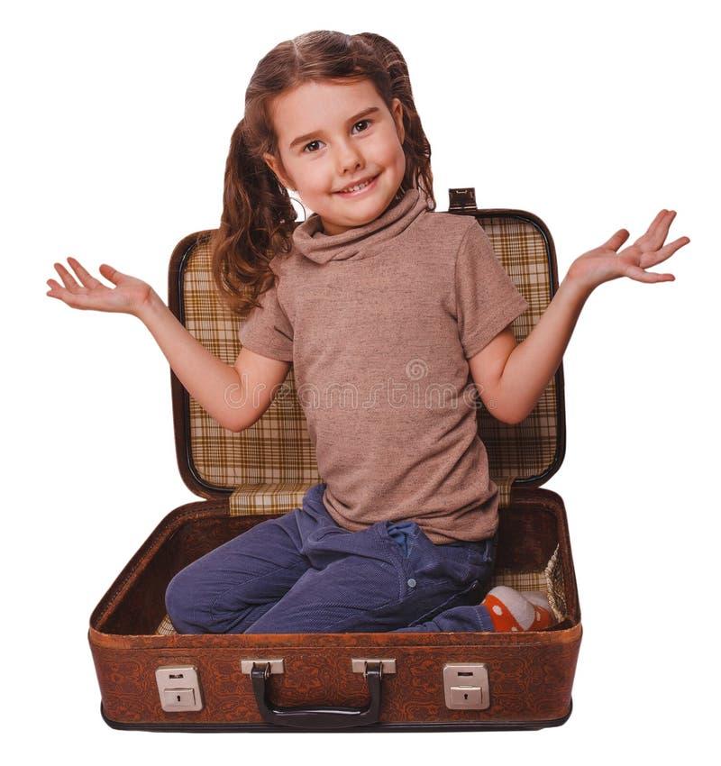 Seduta castana della neonata in una valigia per il viaggio isolata sopra immagine stock