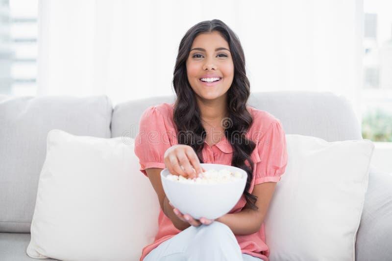 Seduta castana sveglia allegra sulla ciotola del popcorn della tenuta dello strato immagini stock