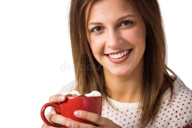 Seduta castana sveglia allegra sulla tazza della tenuta dello strato immagini stock