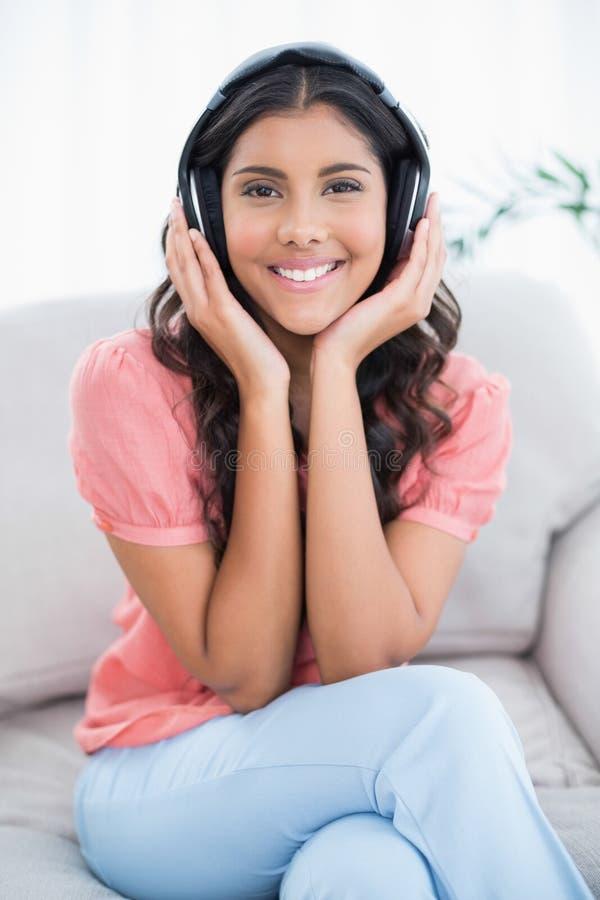 Seduta castana sveglia allegra sullo strato che ascolta la musica immagine stock libera da diritti