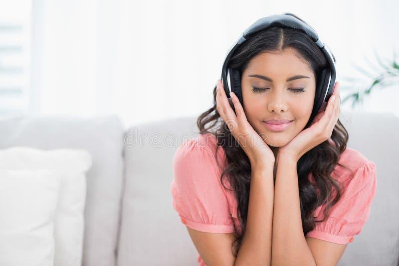 Seduta castana sveglia calma sullo strato che ascolta la musica con gli occhi chiusi fotografia stock