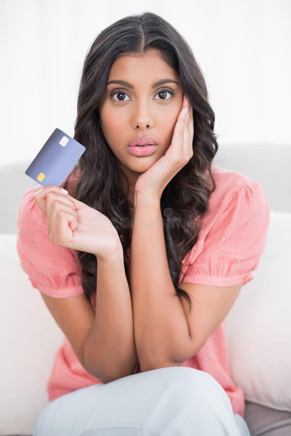 Seduta castana sveglia colpita sullo strato che mostra la carta di credito immagini stock libere da diritti