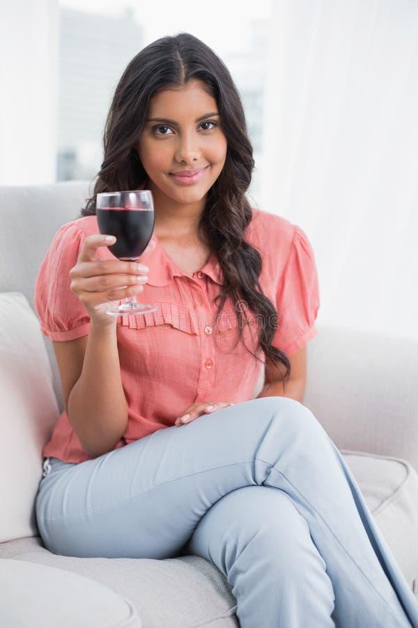 Seduta castana sveglia contenta sul vetro di vino della tenuta dello strato fotografie stock libere da diritti
