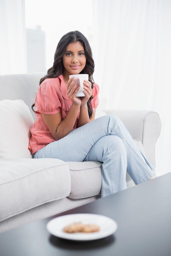 Seduta castana sveglia contenta sullo strato che tiene tazza di caffè immagini stock