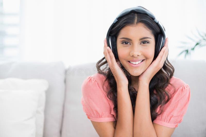 Seduta castana sveglia felice sullo strato che ascolta la musica immagine stock libera da diritti