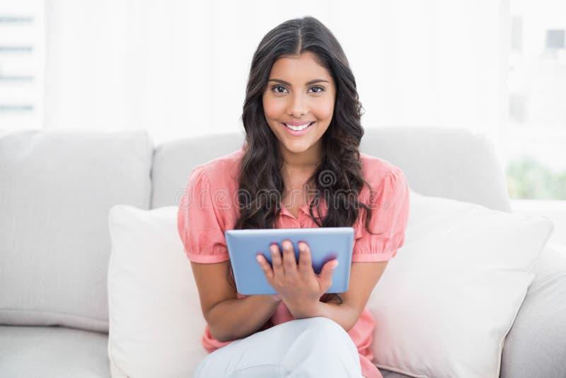 Seduta castana sveglia felice sullo strato facendo uso della compressa immagini stock libere da diritti