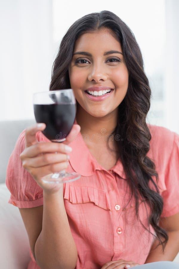 Seduta castana sveglia piacevole sul vetro di vino della tenuta dello strato fotografia stock libera da diritti