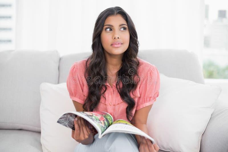 Seduta castana sveglia premurosa sulla rivista della tenuta dello strato fotografia stock