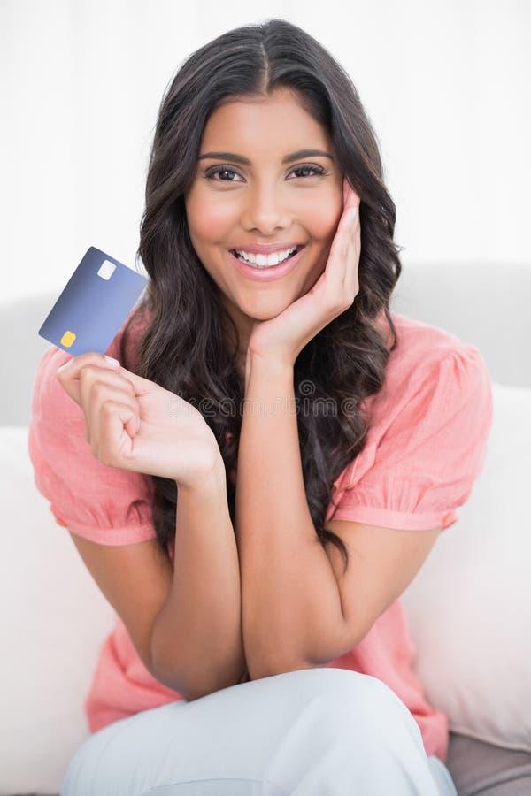 Seduta castana sveglia sorridente sullo strato che mostra la carta di credito fotografia stock libera da diritti