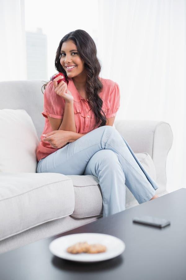 Seduta castana sveglia sorridente sullo strato che tiene mela rossa immagini stock libere da diritti