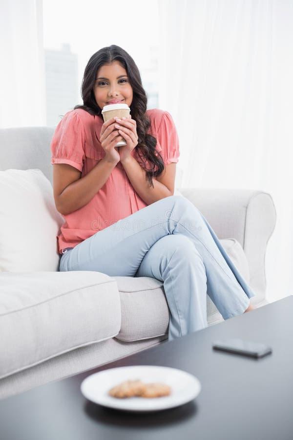Seduta castana sveglia sorridente sullo strato che tiene tazza eliminabile fotografia stock libera da diritti