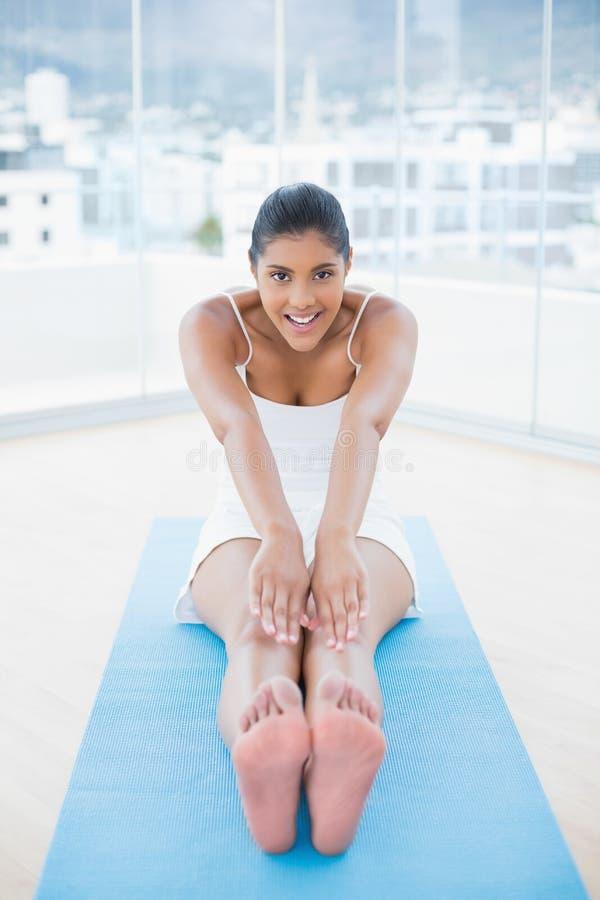 Seduta castana tonificata felice sul pavimento che allunga le gambe immagini stock