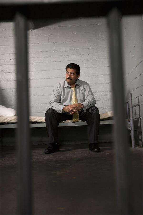 Seduta criminale sul letto in prigione fotografia stock