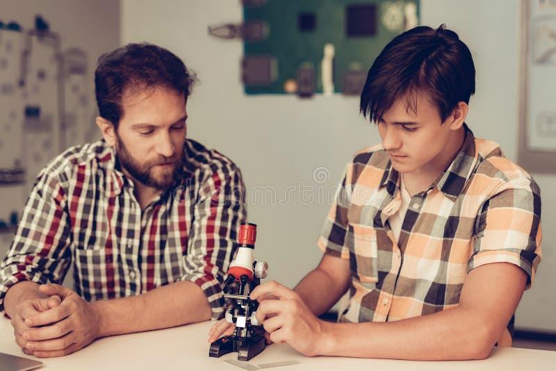 Seduta del figlio vicino al padre ed al microscopio usando fotografie stock libere da diritti