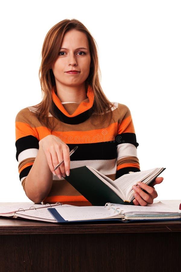 Seduta del libro e della penna della holding della giovane donna fotografia stock libera da diritti