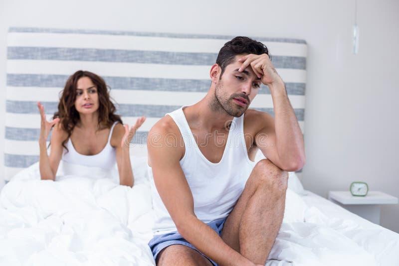 Seduta dell'uomo mentre moglie che grida lui immagini stock libere da diritti