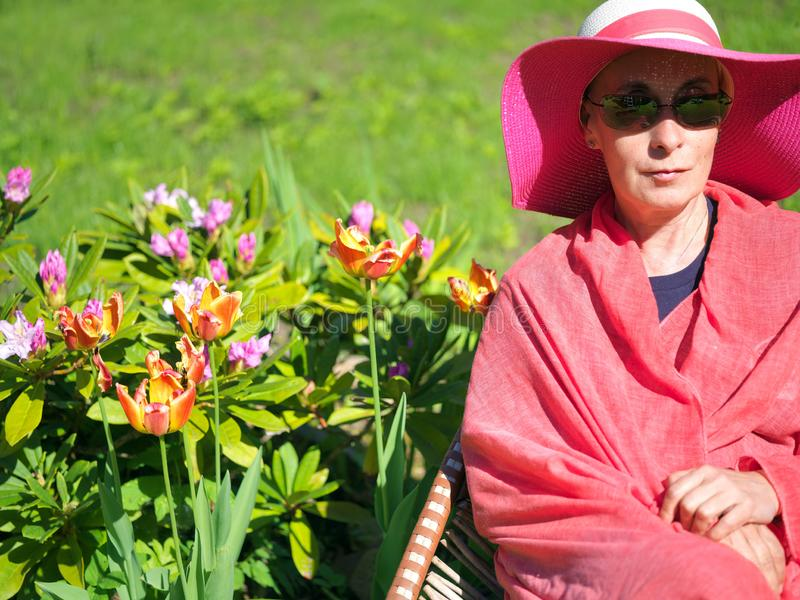 Seduta della donna accanto ai fiori immagine stock