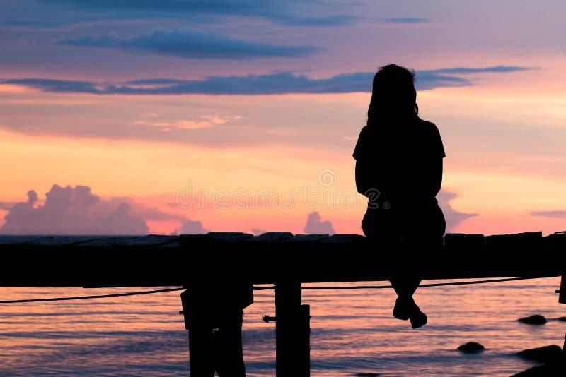 Seduta della donna della siluetta sola fotografia stock
