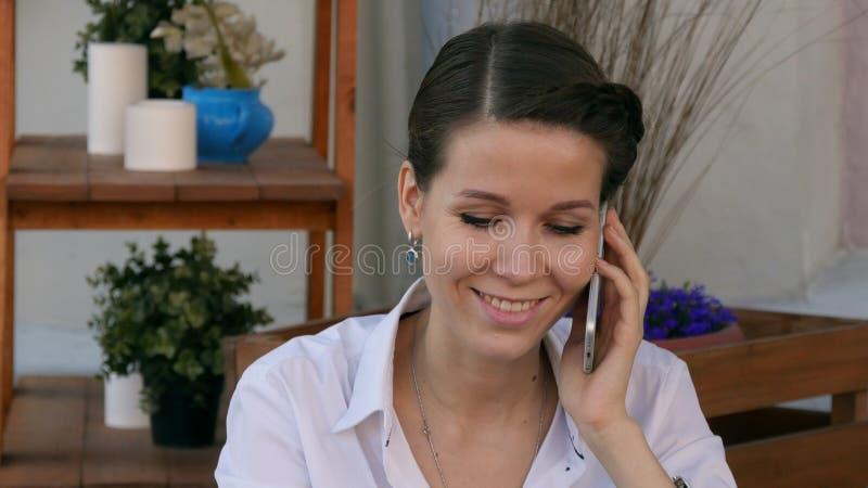 Seduta della donna di affari rilassata al caffè all'aperto che parla facendo uso del suo telefono cellulare fotografie stock