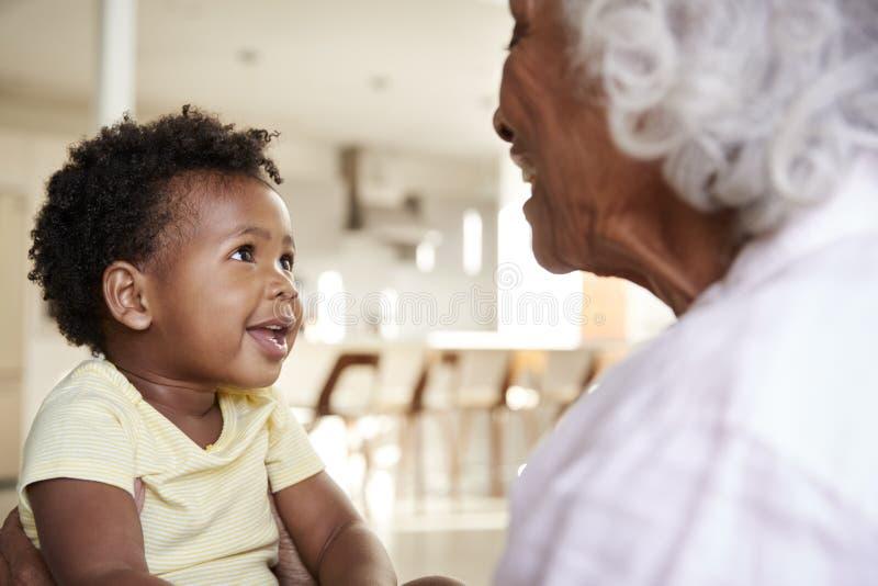 Seduta della nonna sulla nipote di Sofa At Home With Baby che gioca insieme gioco fotografia stock
