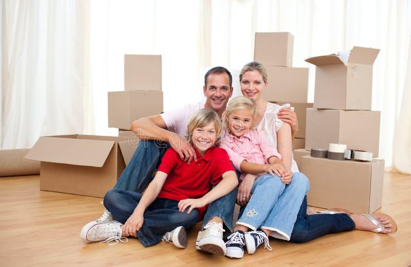 Seduta di distensione sorridente della famiglia sul pavimento fotografia stock libera da diritti