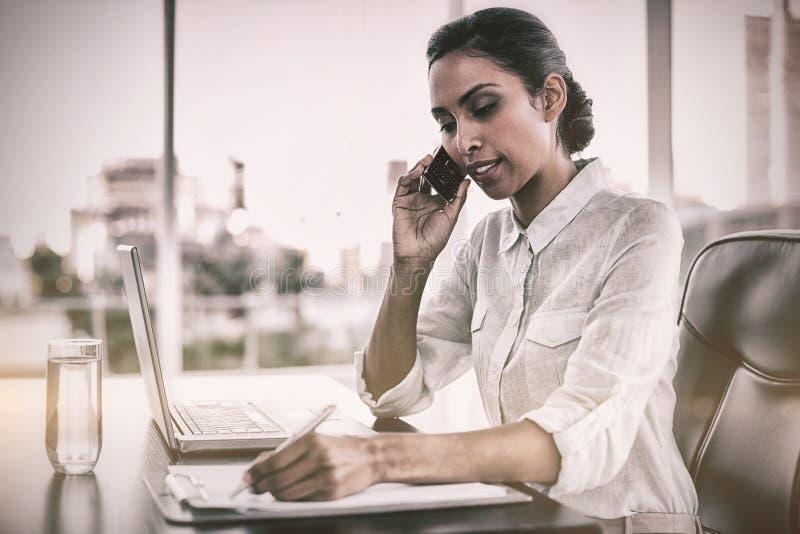 Seduta di lavoro della bella donna di affari al suo scrittorio immagine stock libera da diritti