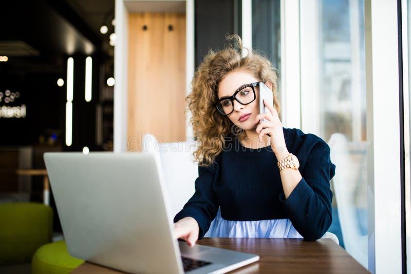 Seduta di lavoro della bella donna di affari al suo scrittorio nell'ufficio Esamini il computer portatile immagine stock libera da diritti