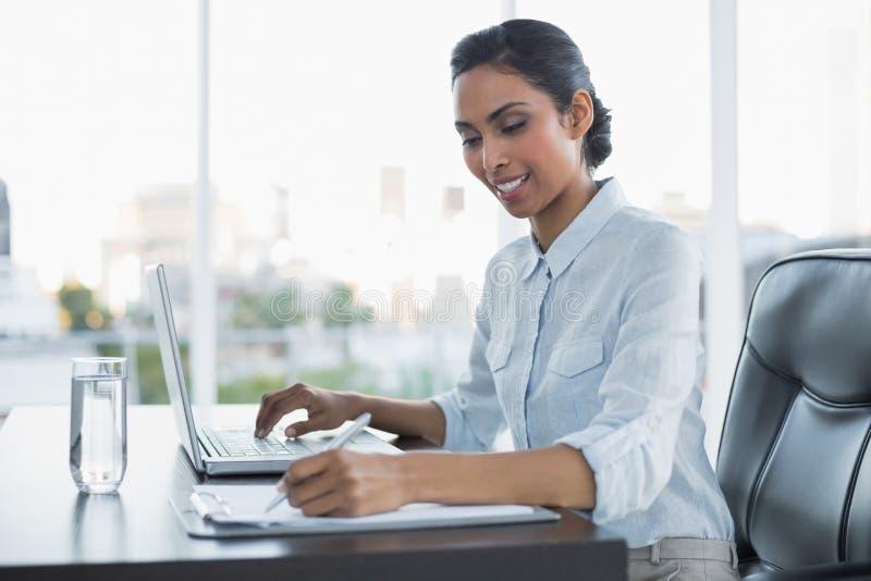 Seduta di lavoro sorridente contenta della donna di affari al suo scrittorio immagine stock