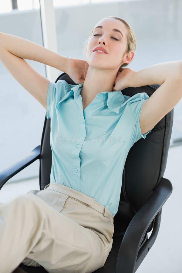 Seduta di rilassamento della donna di affari elegante stanca sulla sua poltrona girevole fotografia stock libera da diritti