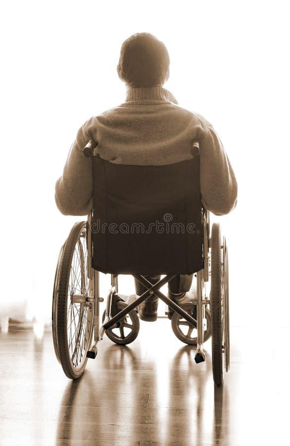 Seduta disabile in una sedia a rotelle nella stanza fotografia stock libera da diritti