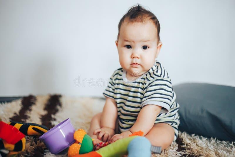 Seduta e gioco della neonata con gli occhi neri ed i capelli neri dei giocattoli fotografia stock libera da diritti