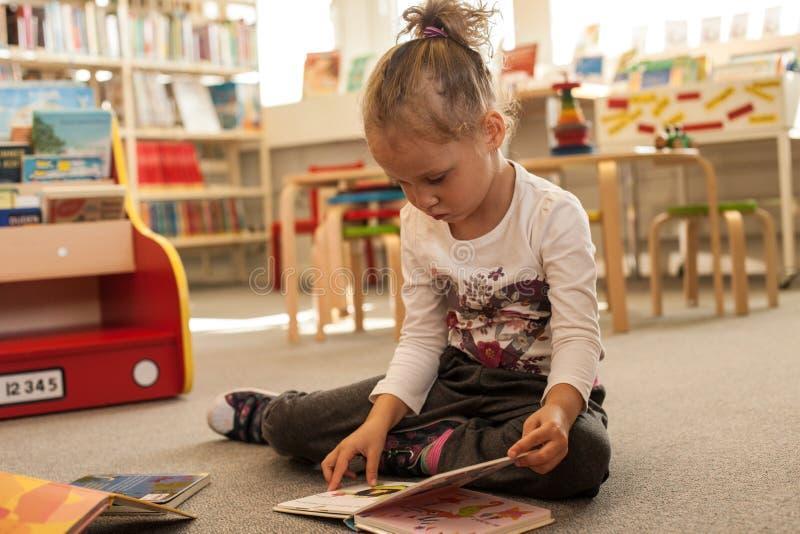 Seduta e lettura della bambina del bambino in età prescolare un libro in biblioteca Bambino con i libri vicino ad uno scaffale Ra immagini stock