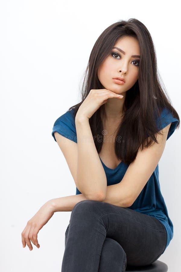 Seduta e lookin asiatici infastiditi della donna alla macchina fotografica su fondo bianco immagini stock