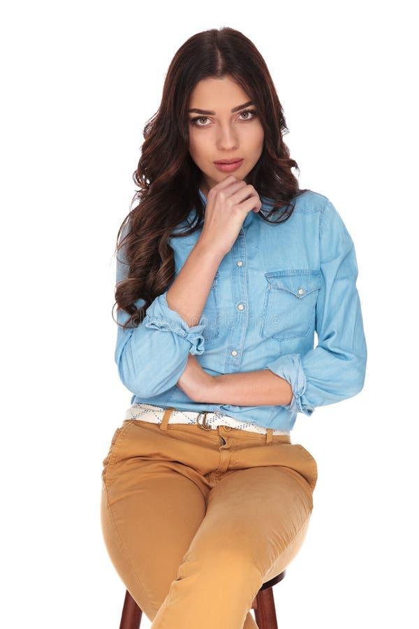 Seduta e pensiero della giovane donna fotografia stock
