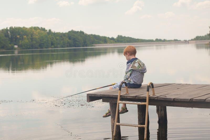 Seduta e pesca del ragazzo da un bacino immagini stock