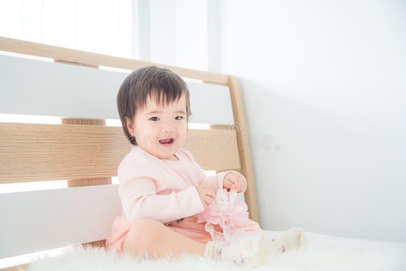 Seduta e sorrisi della bambina sul letto in camera da letto fotografie stock libere da diritti