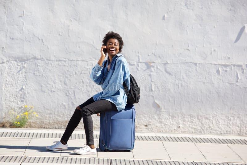 Seduta femminile afroamericana sulla valigia all'aperto e parlando sul telefono cellulare fotografie stock