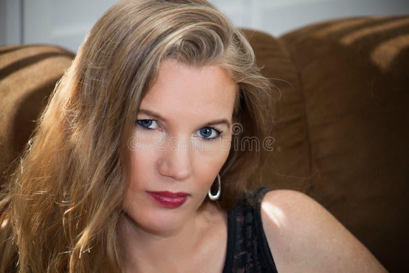 Seduta femminile bionda matura del primo piano su Sofa Looking alla macchina fotografica fotografia stock libera da diritti
