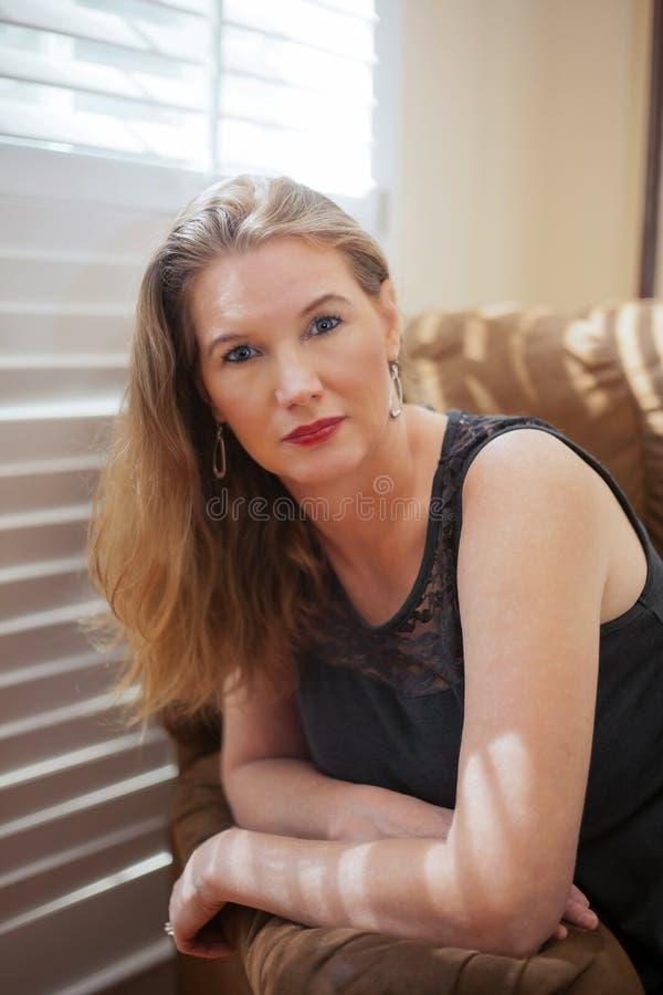 Seduta femminile bionda matura del ritratto del primo piano su Sofa Looking alla macchina fotografica immagine stock