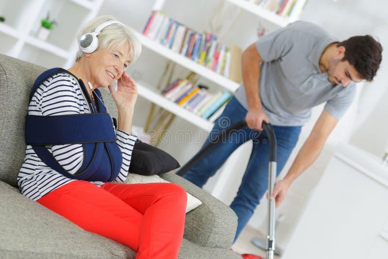 Seduta femminile senior sul sofà mentre pulizia di assistenza domiciliare fotografie stock