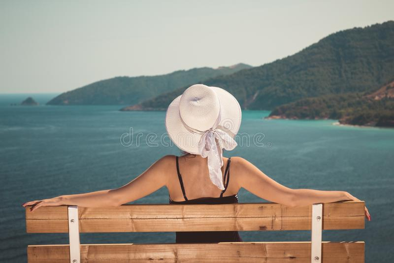 Seduta femminile sul banco e godere della vista del mare fotografia stock