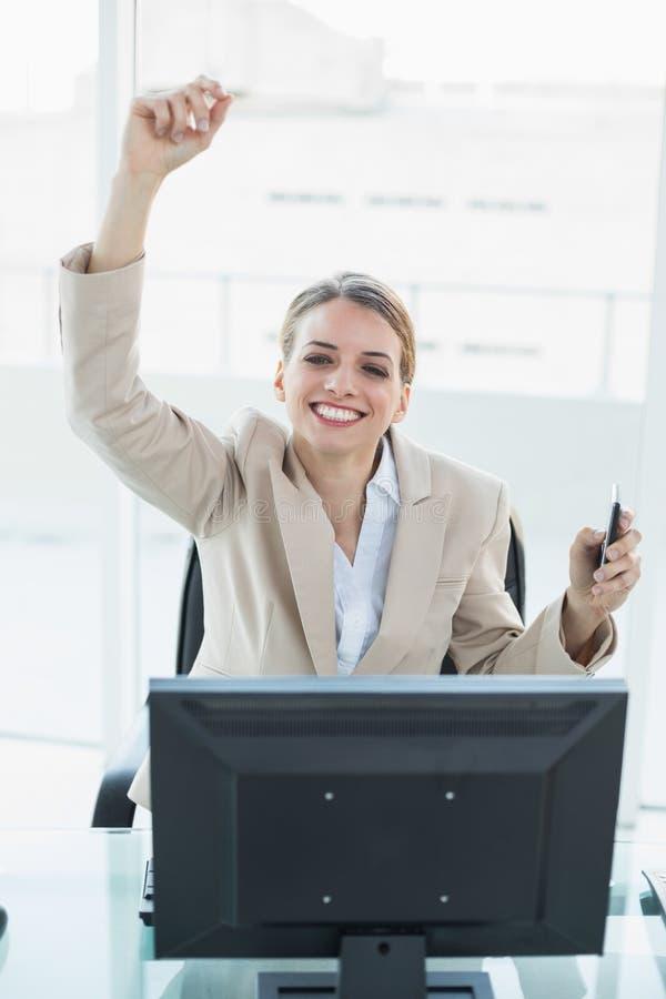 Seduta incoraggiante della donna di affari bionda contenta sulla sua poltrona girevole fotografia stock libera da diritti