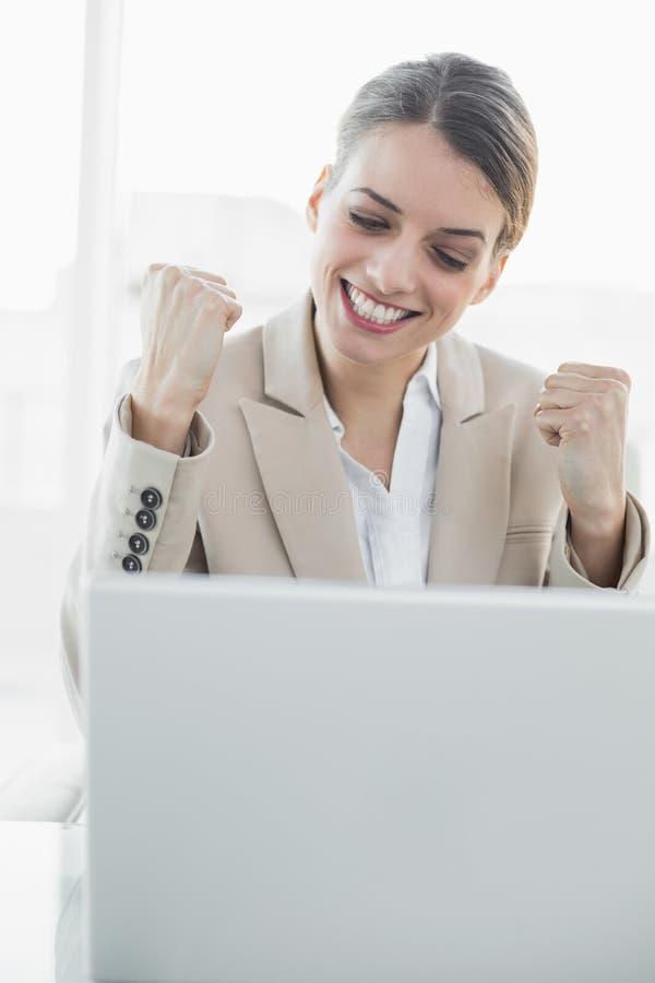 Seduta incoraggiante della giovane donna di affari contenta al suo scrittorio immagine stock