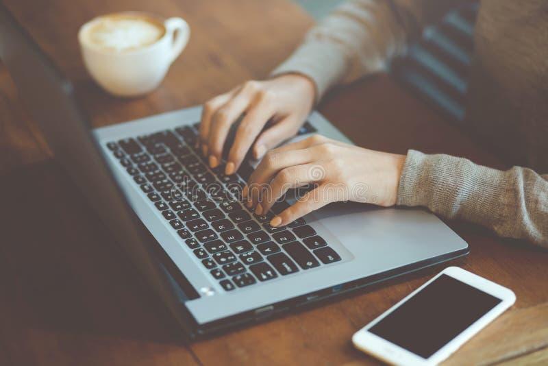 Seduta indipendente della donna di affari facendo uso del lavorare al suo computer portatile del taccuino del computer fotografia stock libera da diritti
