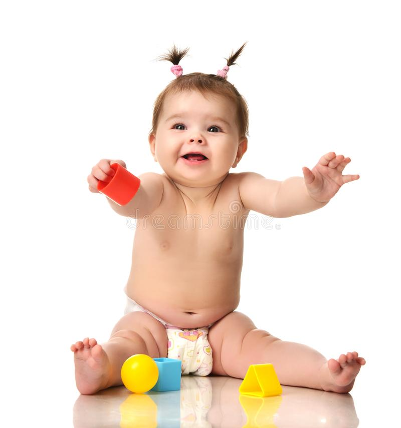 Seduta infantile del bambino del bambino del bambino nuda in pannolino con il gioco educativo blu e rosso giallo dei giocattoli i immagine stock libera da diritti