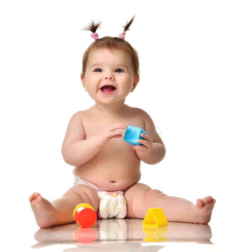 Seduta infantile del bambino del bambino del bambino nuda in pannolino con il gioco educativo blu e rosso giallo dei giocattoli i immagini stock