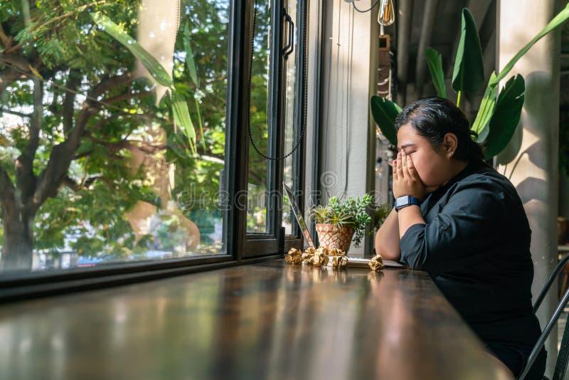 Seduta lesbica sola con le palle di carta sgualcite nel posto rustico fotografie stock libere da diritti